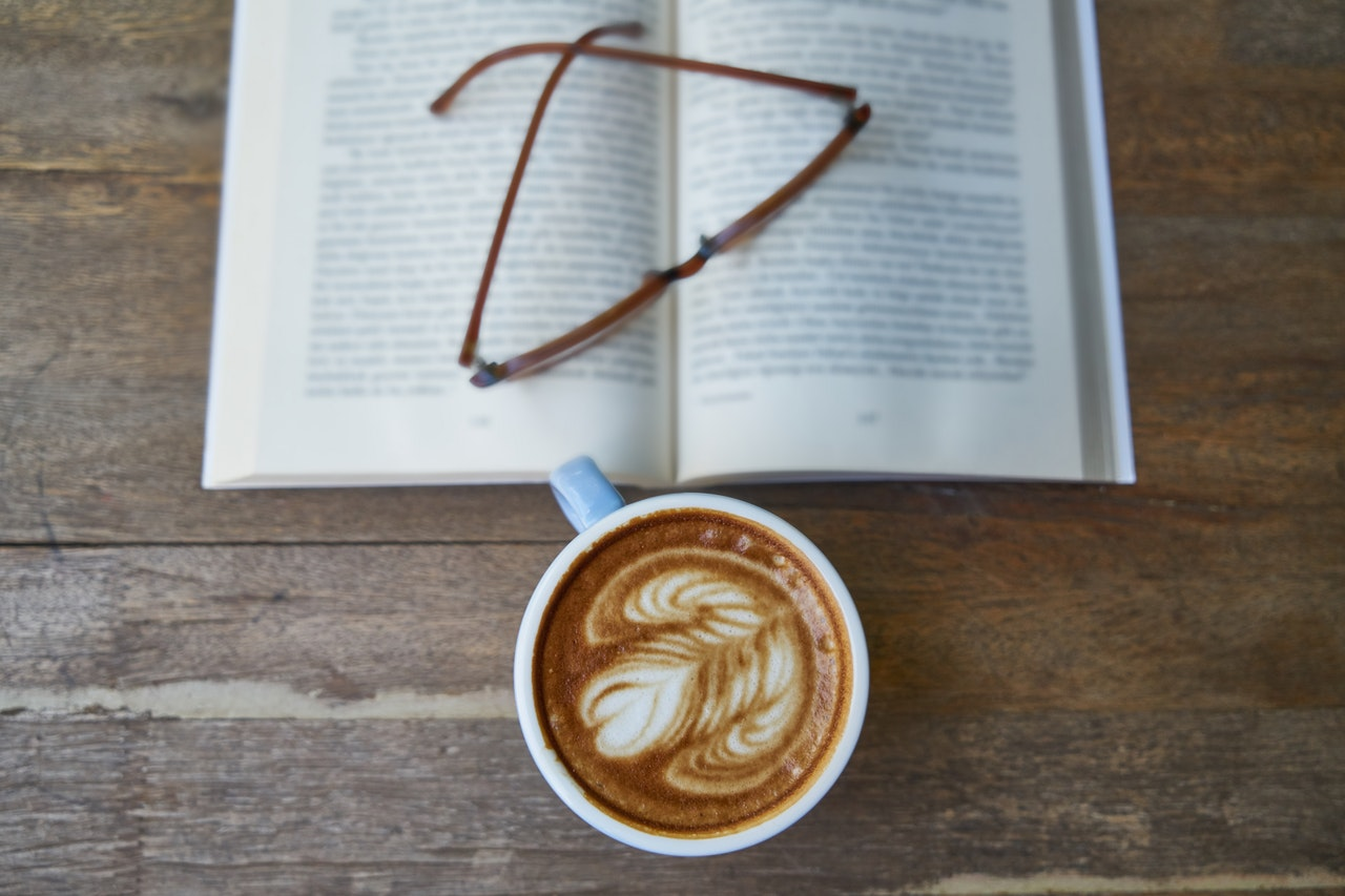 a cup, spects, and a book.