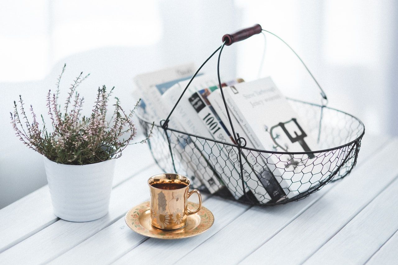a cup and books in a basket