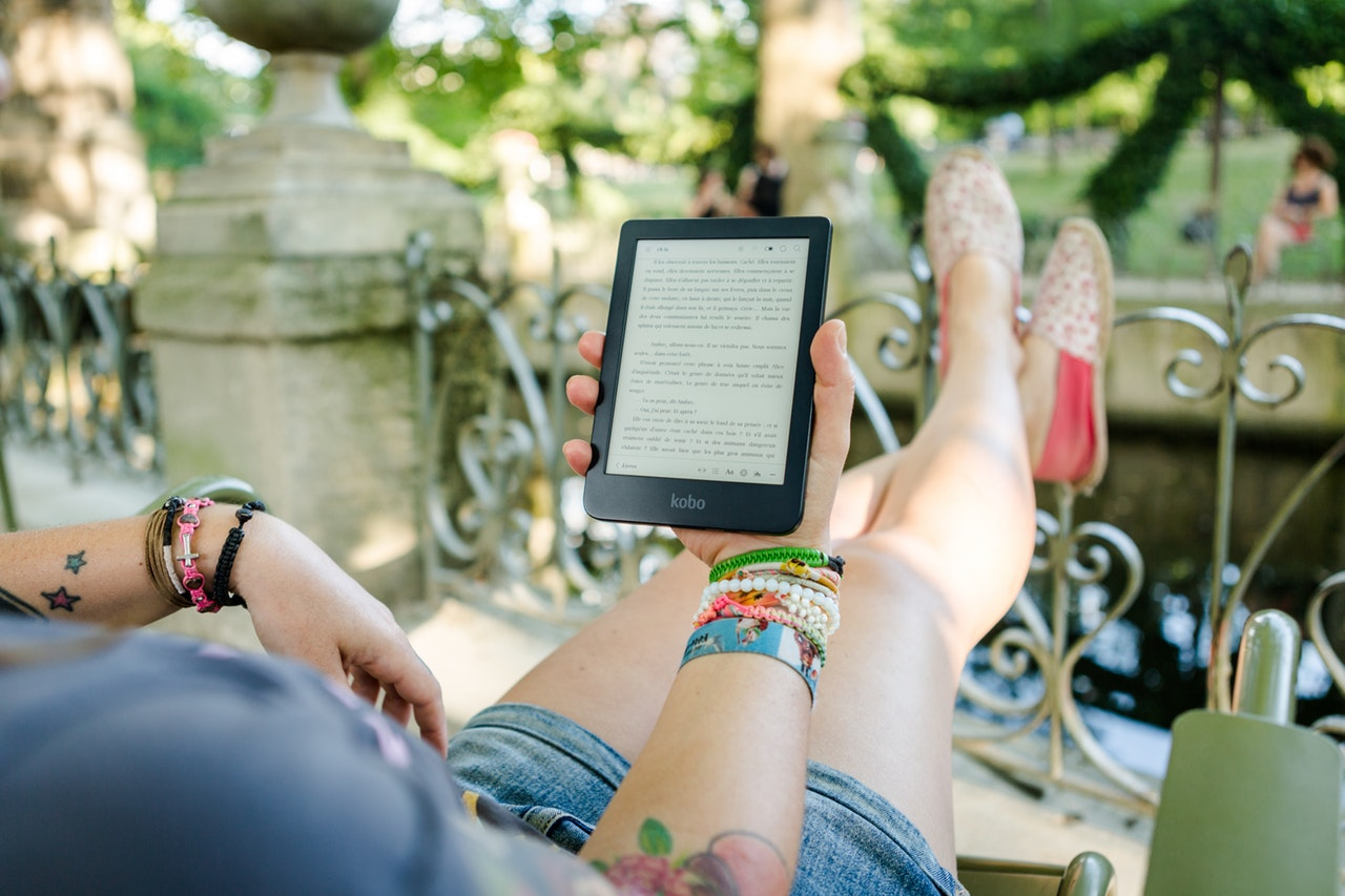 a person reading on a tablet/Reading Gadgets